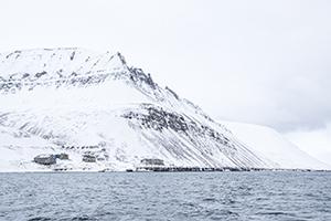verschneite Bergkette und kleine Häuser auf Svalbard, Barentsburg